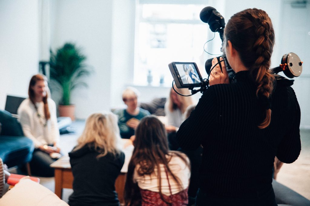 Woman holding video camera recording people